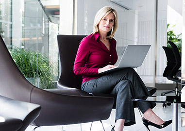 Financially independent woman using computer in an office.