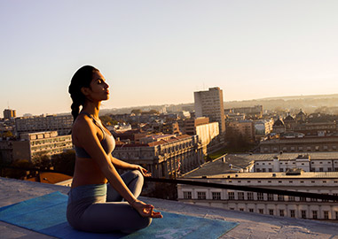 Woman meditating on a roof outside
