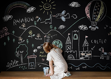 Young girl drawing on a on a chalk board, creating a passion board